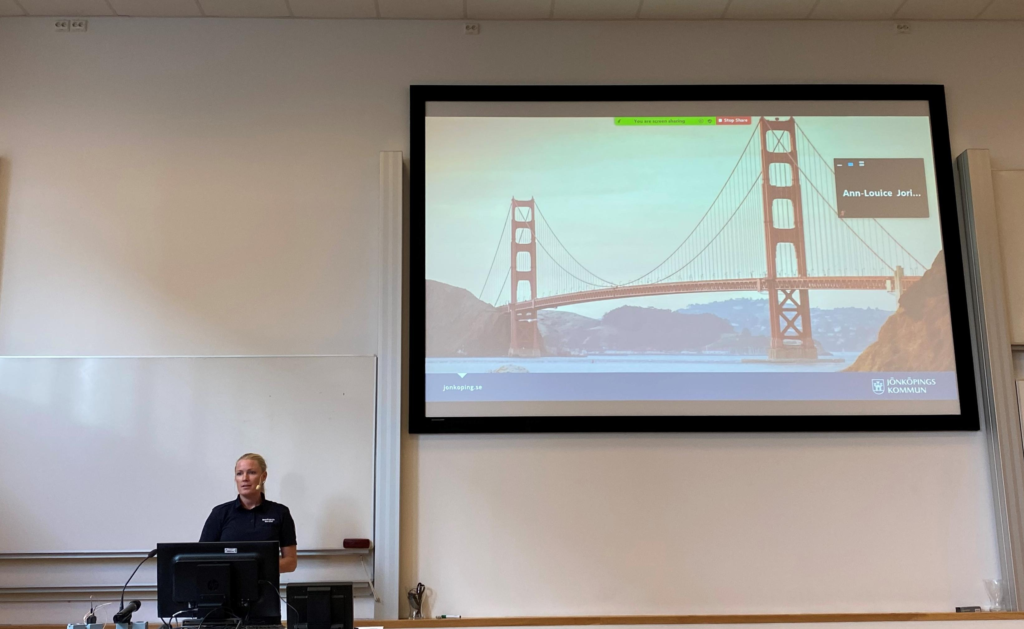 Elin Isfall, presenting and showing an image of the Golden Gate bridge in San Fransisco on the screen.