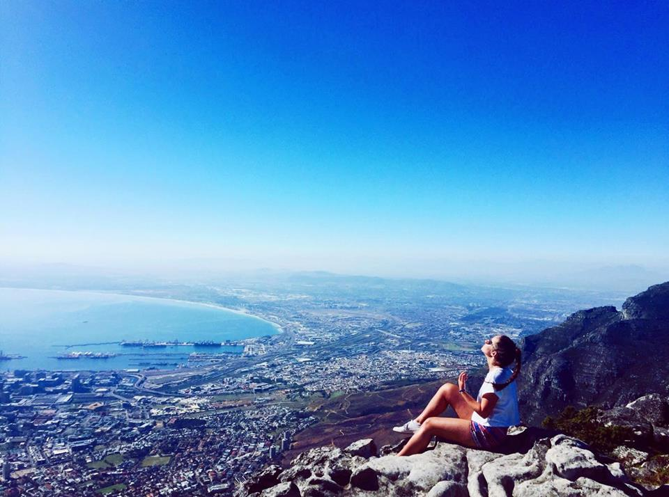 Woman on mountainside with a beautiful view of the South African coast