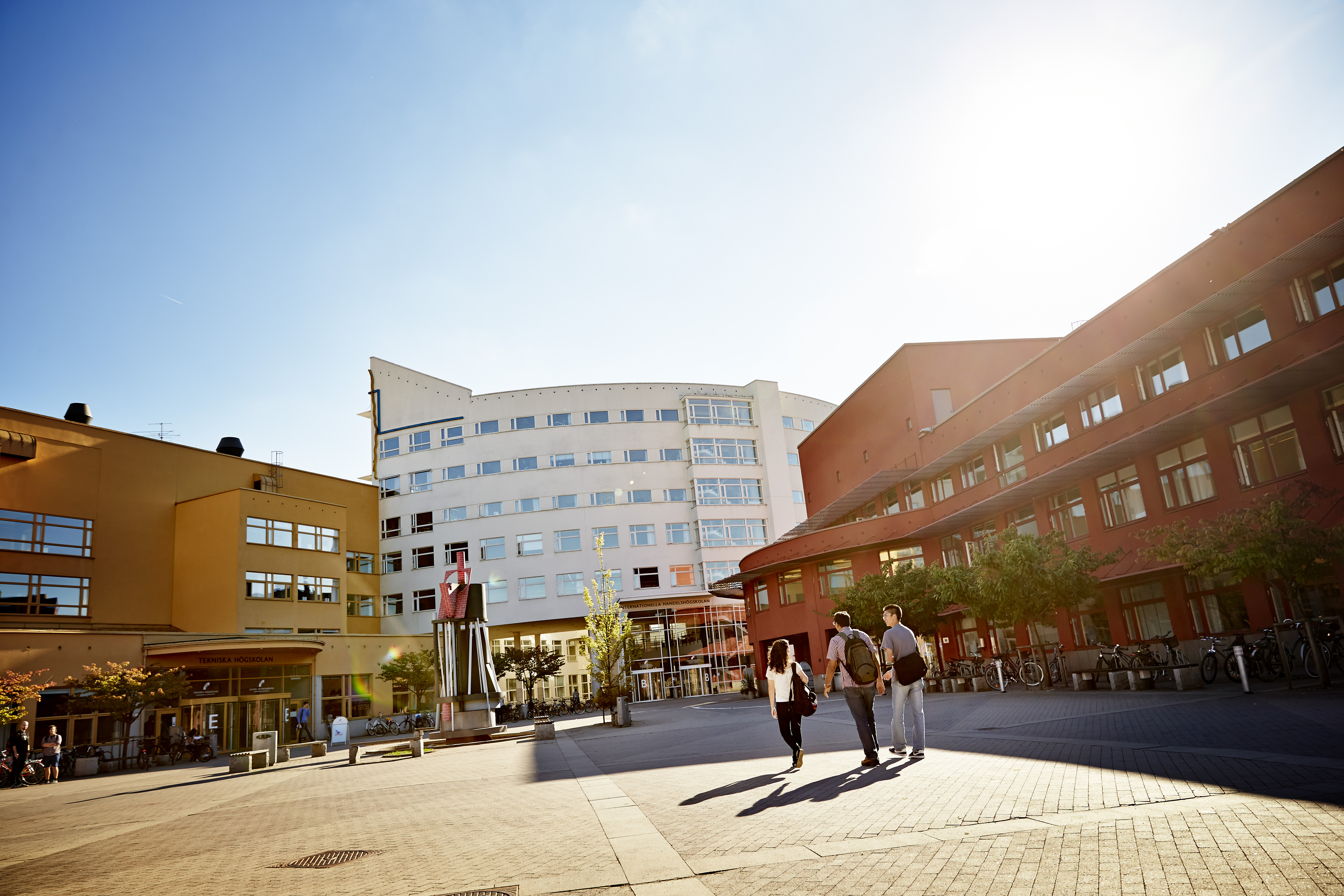 Tre studenter på campus en solig dag